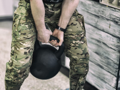 Abstract athlete in camouflage pants with weights, lifting a heavy weight in a gym